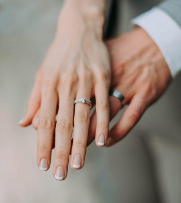 Hands overlapping wearing wedding bands