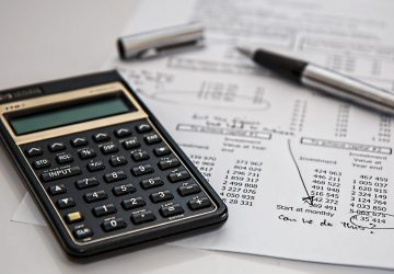 Calculator and pen on top of account working out budget